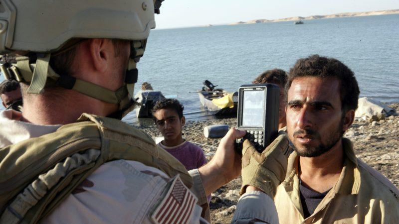 U.S. military member using a handheld biometric scanner to take a subjects iris scan